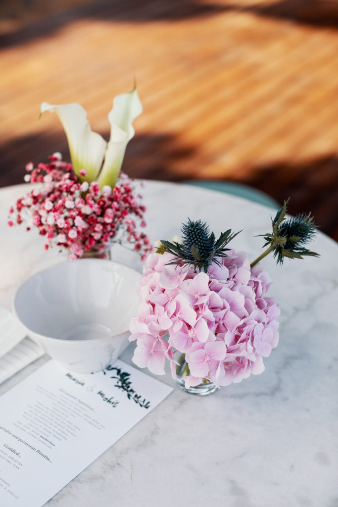 cocktail table with centerpieces with pink flowers, white lilies, and menu, Blanes, Spain