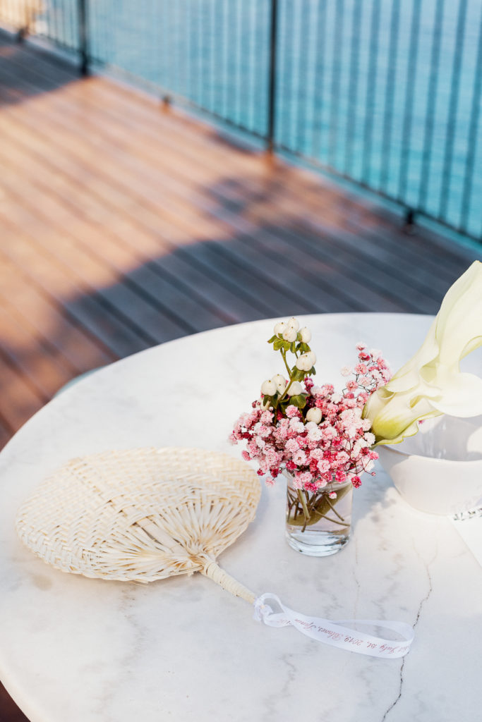 wedding cocktail table with pink floral arrangement and woven palm hand fan, Barcelona Brides