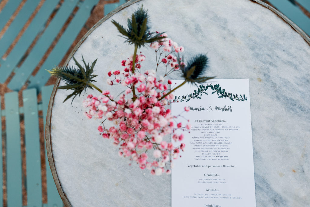 wedding cocktail table with pink floral arrangement and menu, Barcelona Brides
