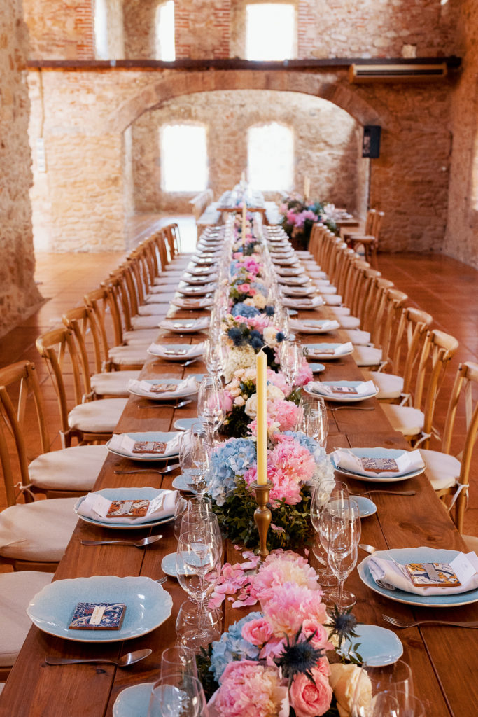 wedding table with blue place settings, and blue and pink flowers in the convent in Blanes, Spain