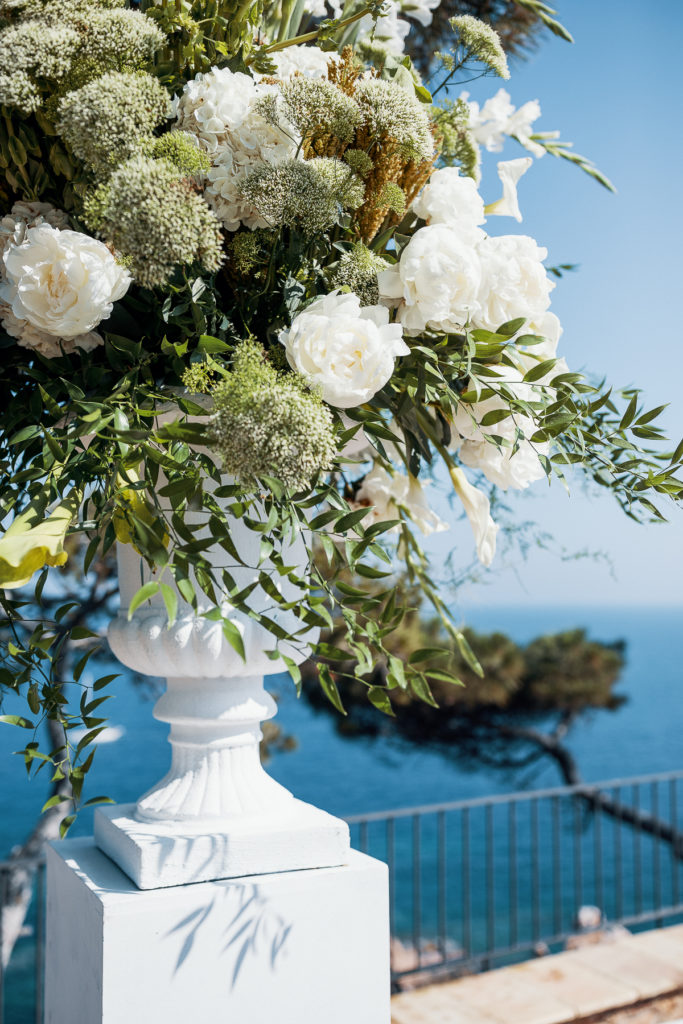 white pillar filled with large all white floral arrangement for wedding at convent of Balmes, Spain