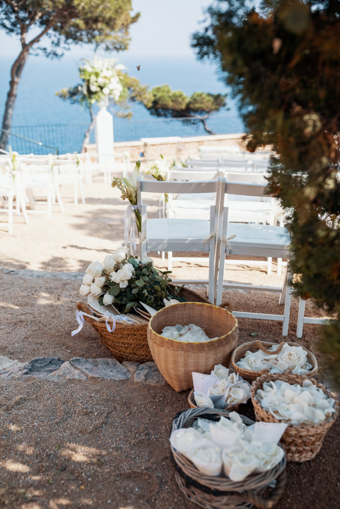 white wedding guest chairs with white floral decoration and baskets filled with flowers and petals for tossing at convent of Balmes, Spain