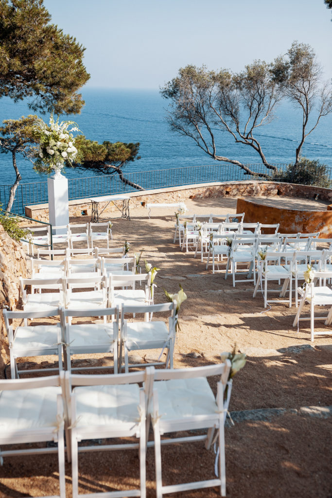 white chairs for wedding guests facing altar and sea on the terrace of convent of Balmes, Spain