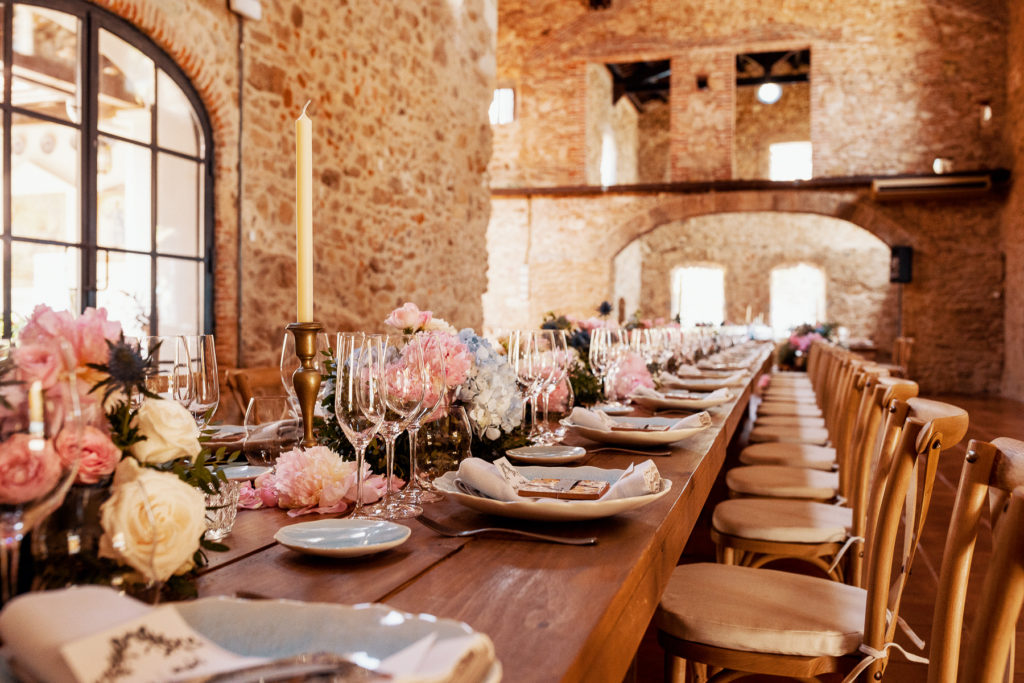 dining table with light blue place setting, pink and blue flowers and candles at convent in Blanes, Spain