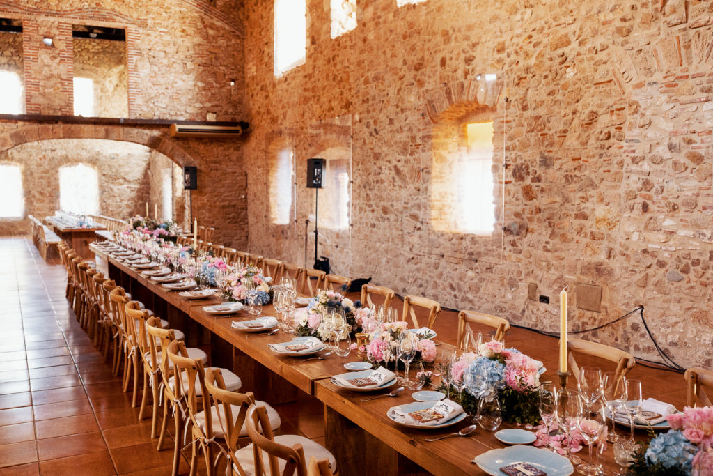 wedding dining table with light blue place settings, blue and pink flowers, and candles at Blanes convent, Spain