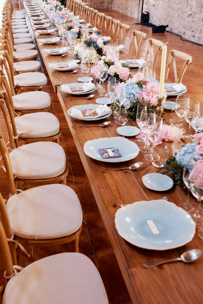 wedding table with light blue plates, pink and blue flowers, cream candles, convent in Blanes, Spain