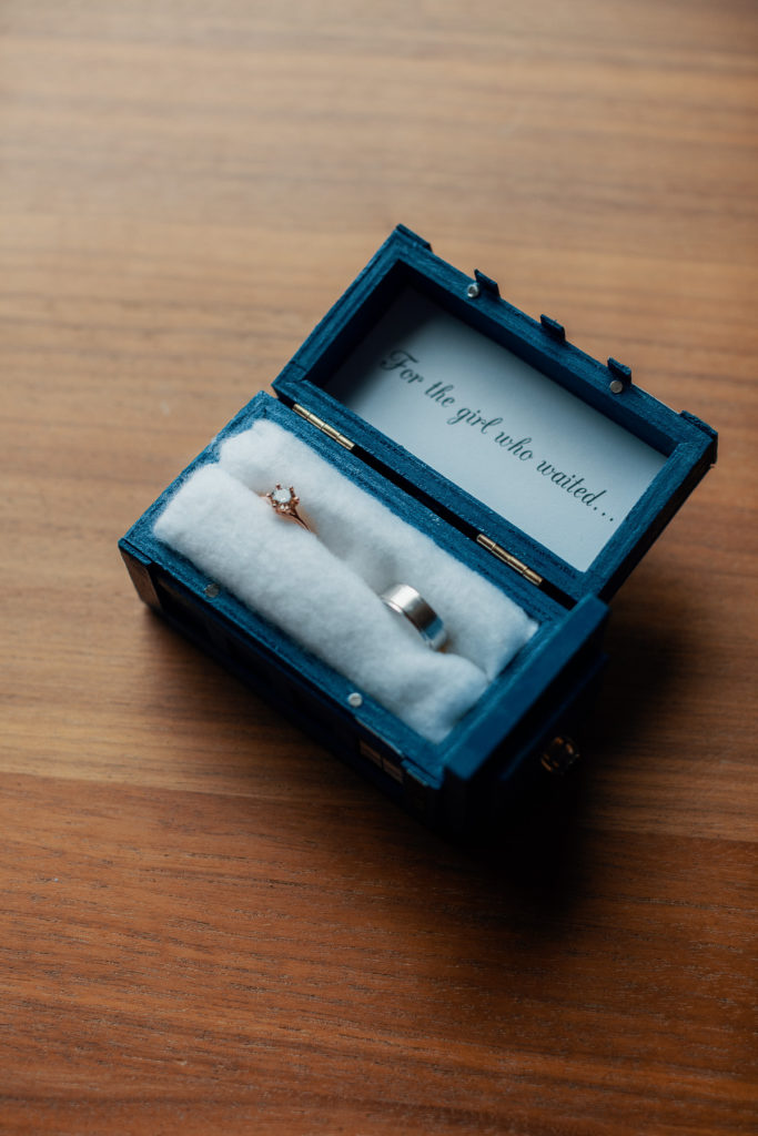 ring box with wedding rings that says for the girl who waited on the inside