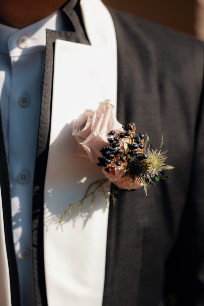 boutonniere made with light pink rose, dark berries, and wild grass