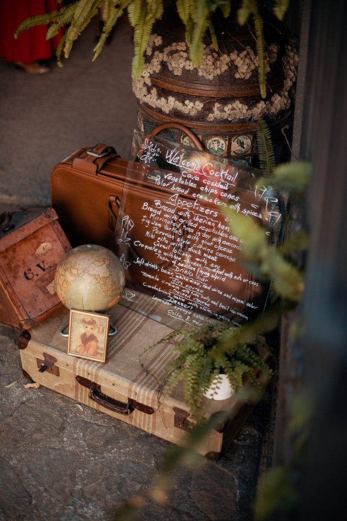 wedding menu written on plexiglass on top of old suitcases with a globe