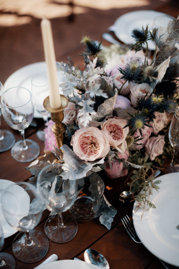 wedding floral arrangement with light pink and purple flowers and cream colored candlesticks