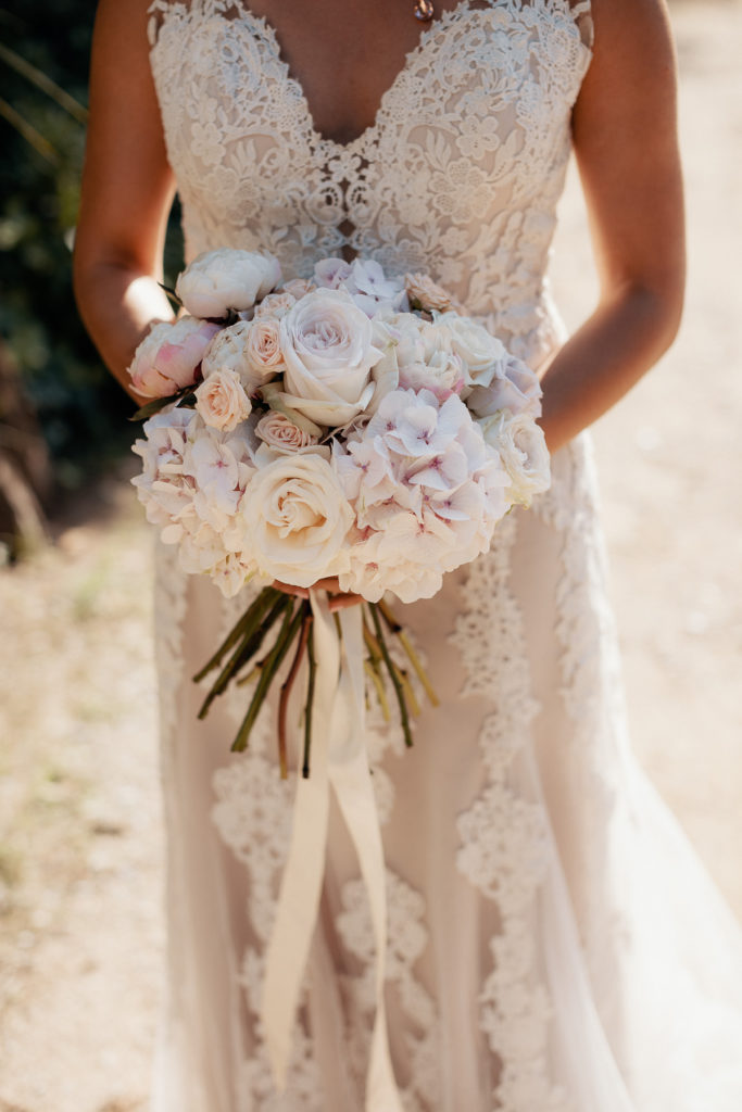 bride in lace wedding dress holding bouquet of light pink and white flowers