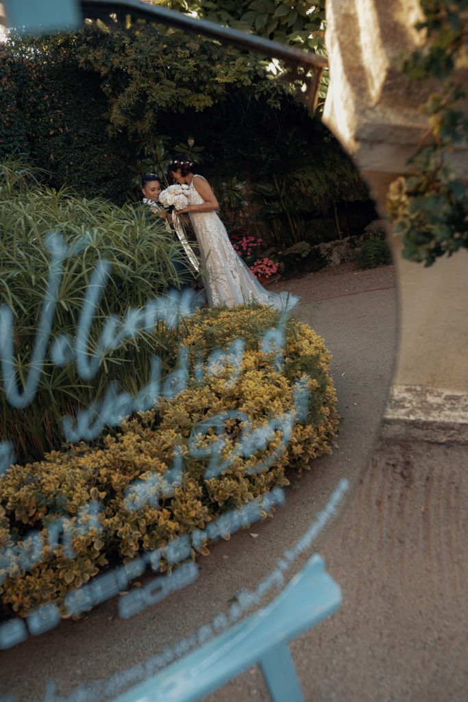bride and groom in the garden reflected in a mirrored welcome sign