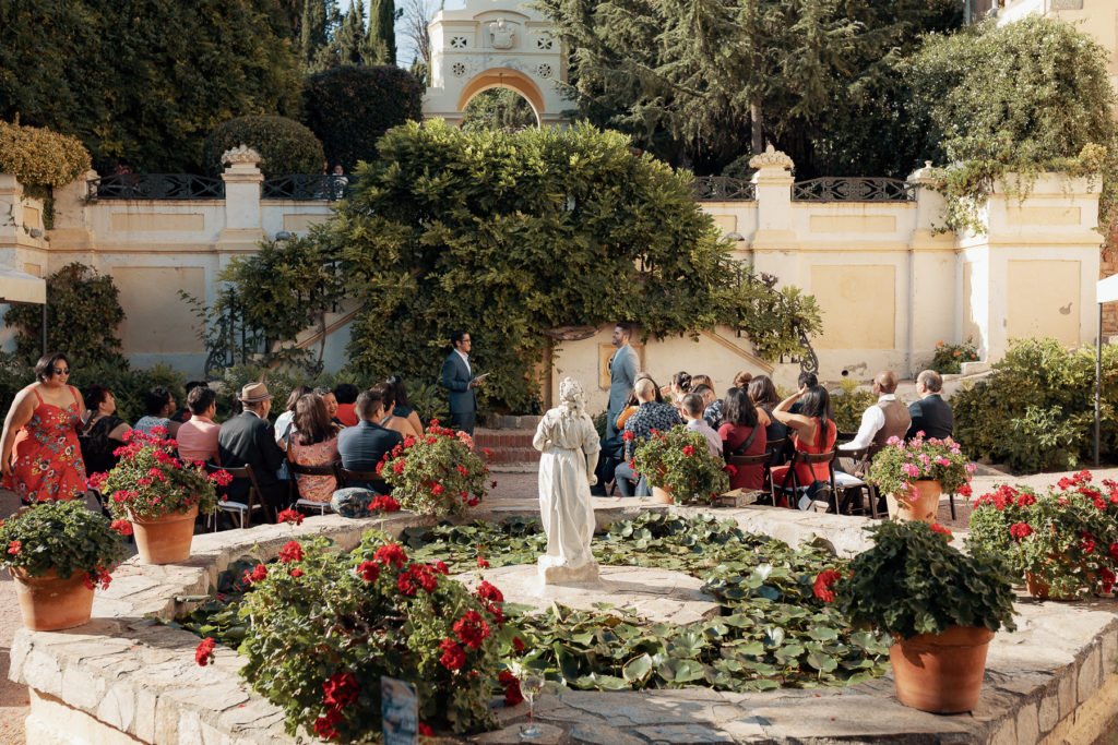 groom waits for the bride in front of guests near a marble fountain