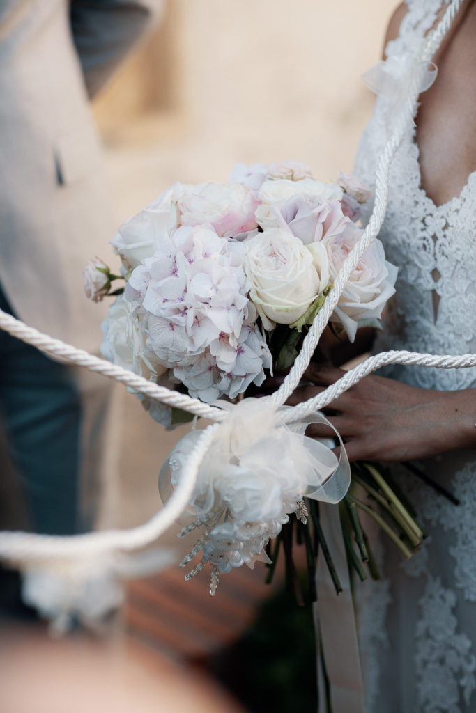 bride holds bouquet of light pink and white flowers