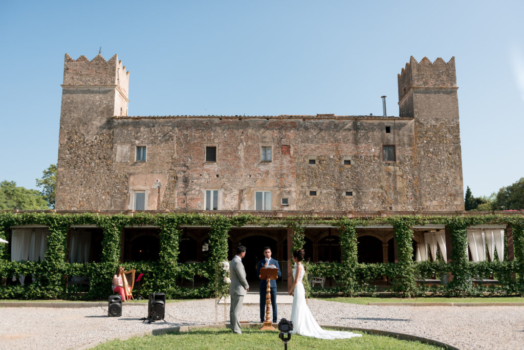 bride and groom in front of castle with master of ceremony