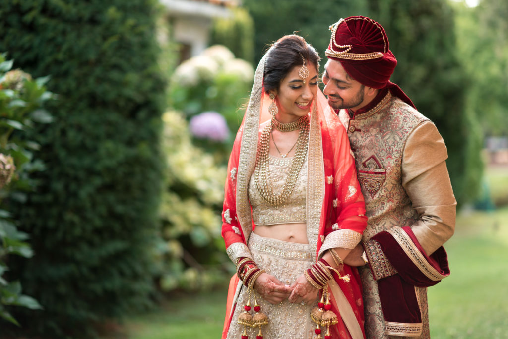 Hindi couple embracing in traditional gold and red clothing