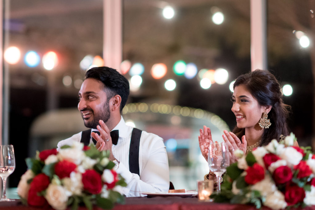 bride and groom applaud at dinner table