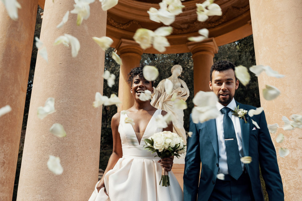 bride and groom in labyrinth park barcelona spain with white rose petals falling