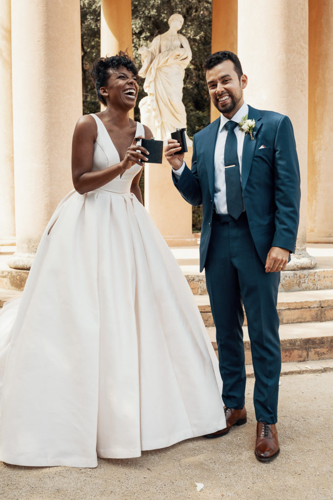 bride and groom smile and hold flasks in the labyrinth park barcelona spain
