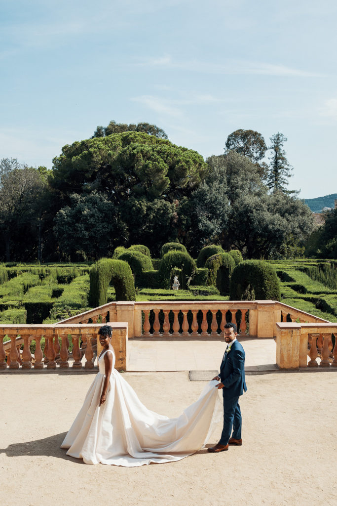 groom holds bride's train in front of the labyrith park barcelona spain