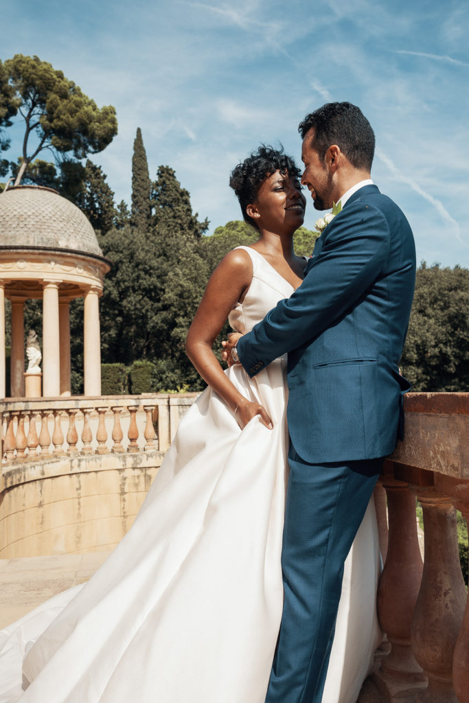 groom embraces bride on balcony in labyrinth park barcelona spain