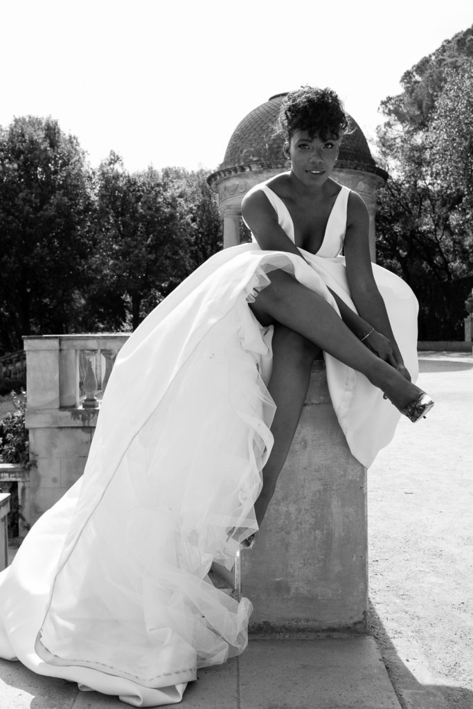bride sits on wall and adjust her shoe in the labyrinth park barcelona spain