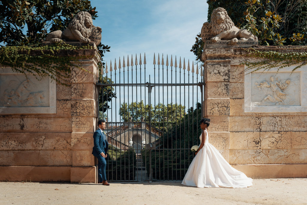 bride and groom stand outside gate of labyrinth park barcelona spain