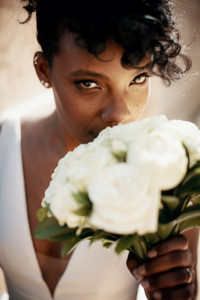 bride smells her bouquet made of white roses