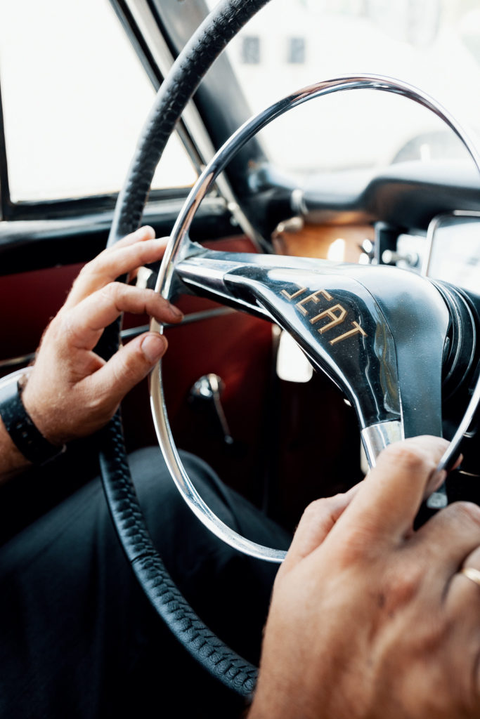 hands on old fashioned steering wheel that says seat in the middle