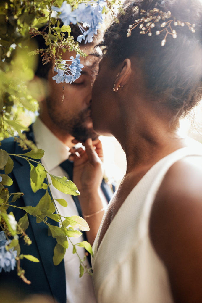 bride and groom kiss amongst flowers in labyrinth park barcelona spain