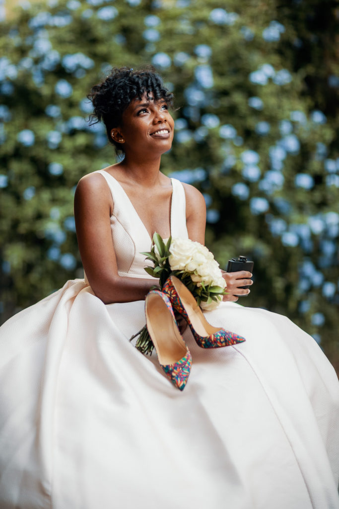 bride holds high heel shoes and her bouquet in her hands in the labyrinth park barcelona spain