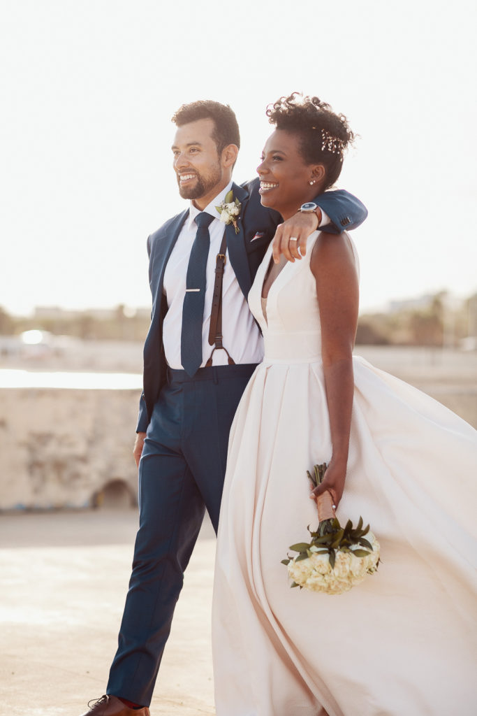 brides and groom smile on pier in barcelona spain