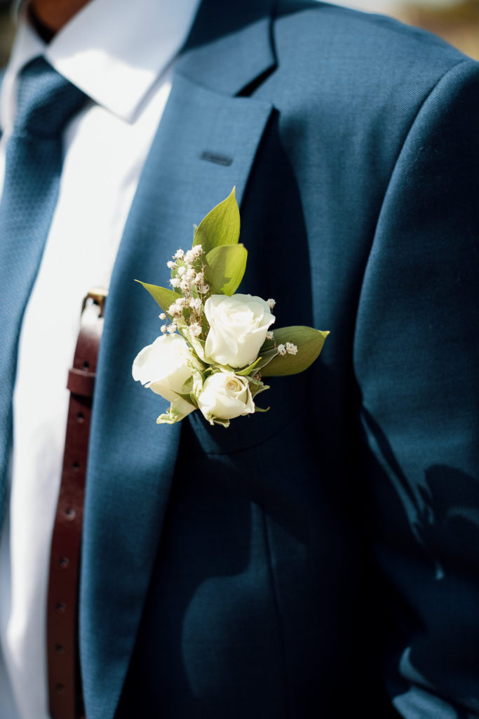 boutonniere made of white roses and babys breath on mens suit