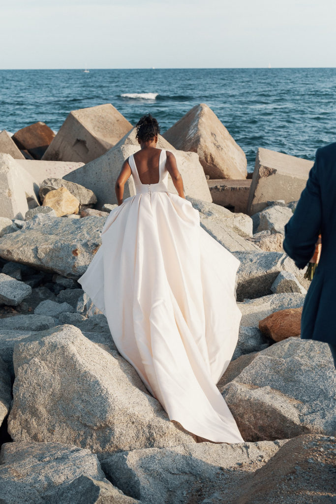 bride holds dress and walks on concrete blocks in sea in barcelona spain
