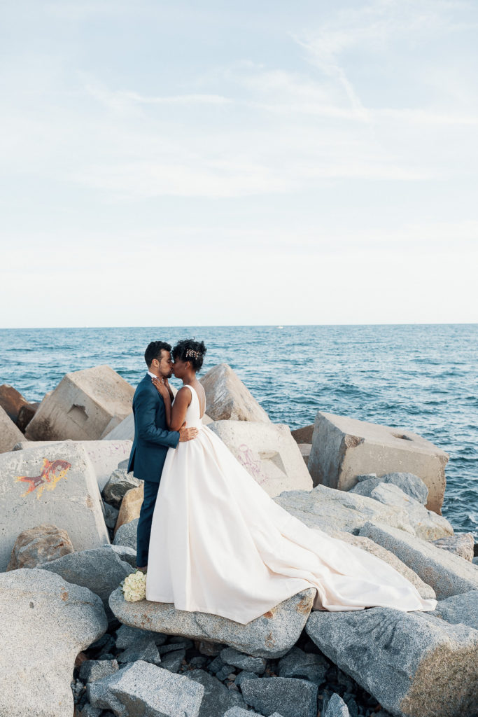 bride and groom kiss on concrete blocks in the sea barcelona spain