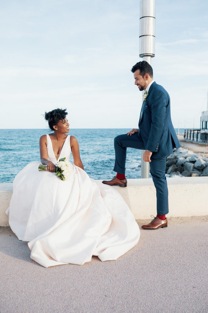 bride sits on wall and groom stands beside her on pier in barcelona spain