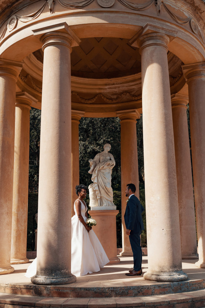 bride and groom stand under dome with a marble sculpture in the labyrinth park barcelona spain
