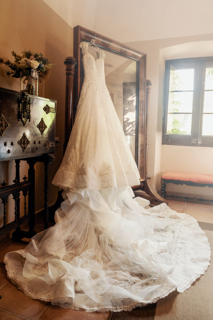 wedding gown hanging on mirror inside castell de tamarit, barcelona, spain