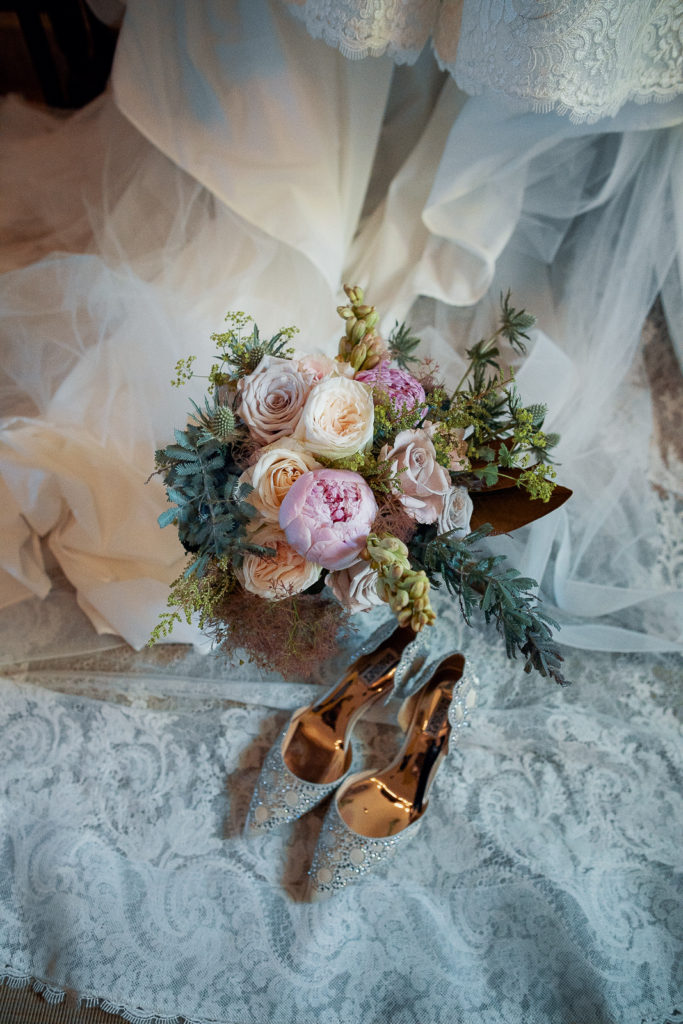 colorful bridal bouquet with bride's shoes and dress, castell de tamarit, barcelona brides
