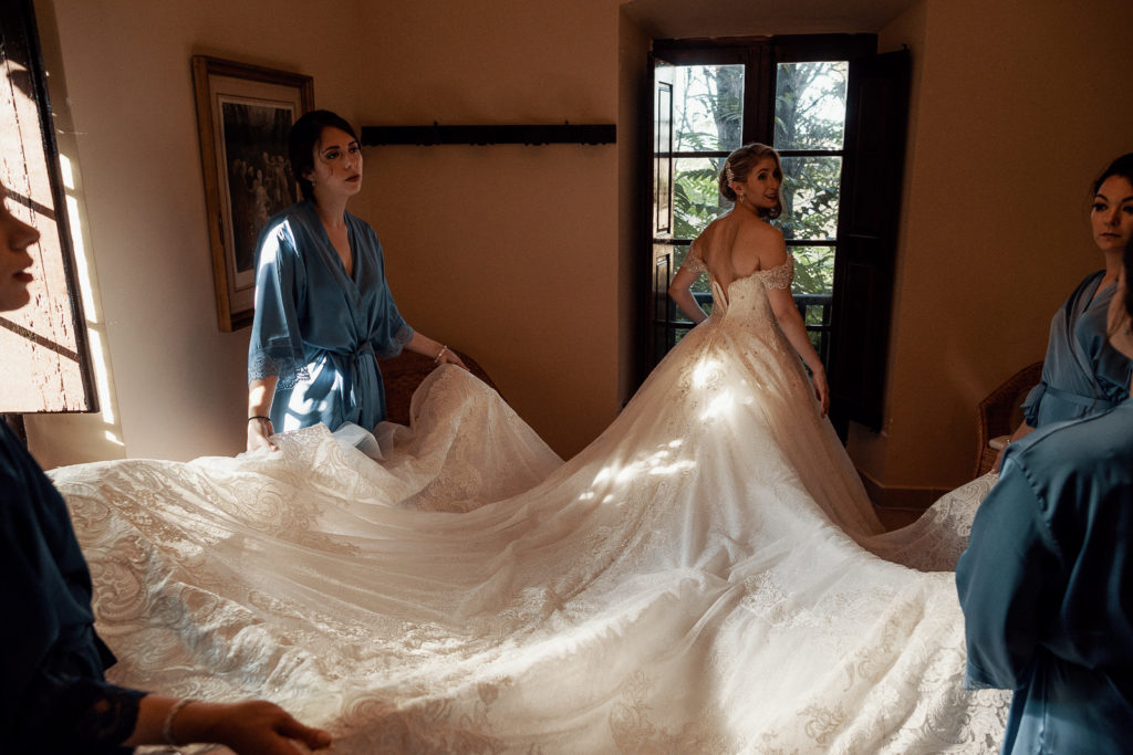 bridesmaids hold bridal dress train, castell de tamarit, barcelona, spain