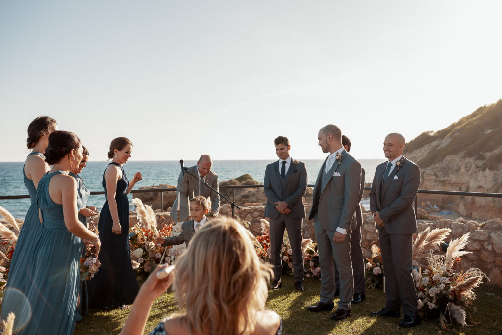 groomsmen and bridesmaids on terrace overlooking sea, castell de tamarit, barcelona, spain