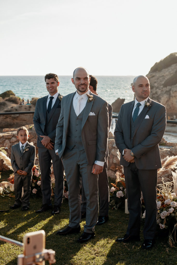 groom and groomsmen near the sea outside castell de tamarit, barcelona, spain