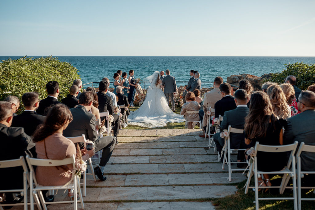 bride, groom, and guests in ceremony in front of sea, castell de tamarit, barcelona, spain