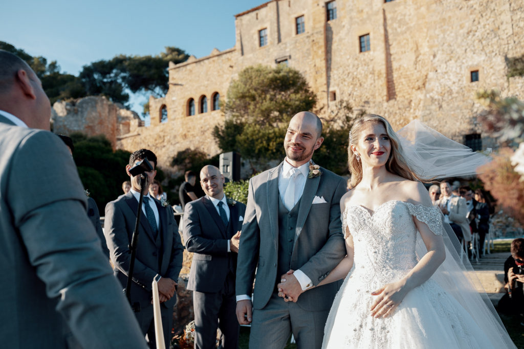 bride and groom hold hands outside castell de tamarit, barcelona, spain