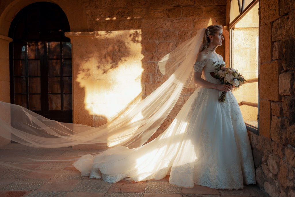 bride looks out window in dress and veil, castell de tamarit, barcelona, spain