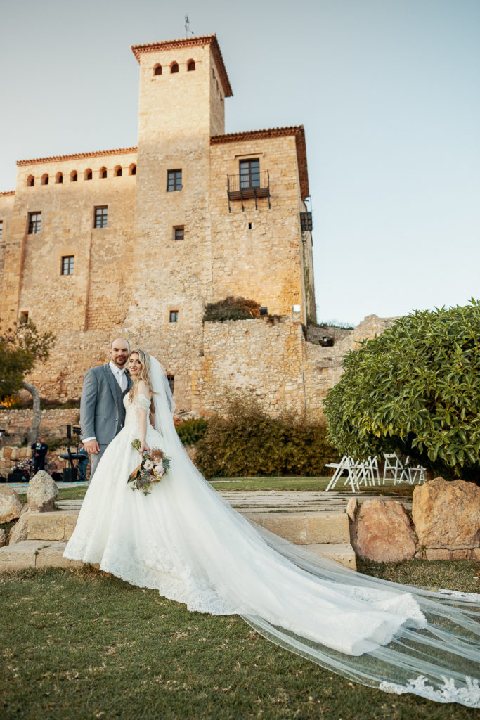 bride and groom in front of castell de tamarit, barcelona, spain