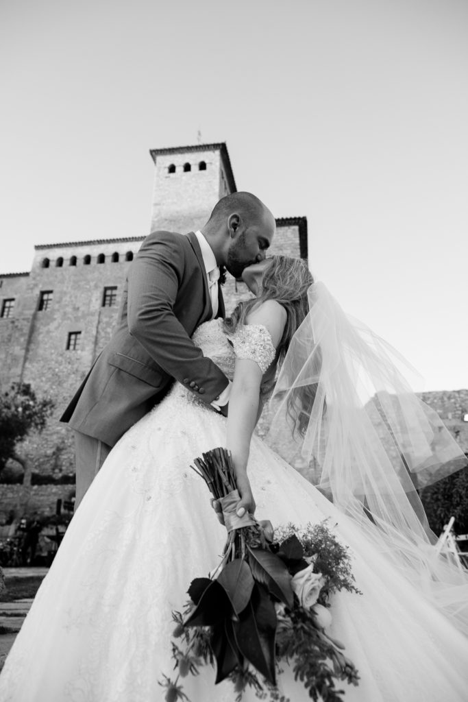 bride and groom kiss outside castell de tamarit, barcelona, spain