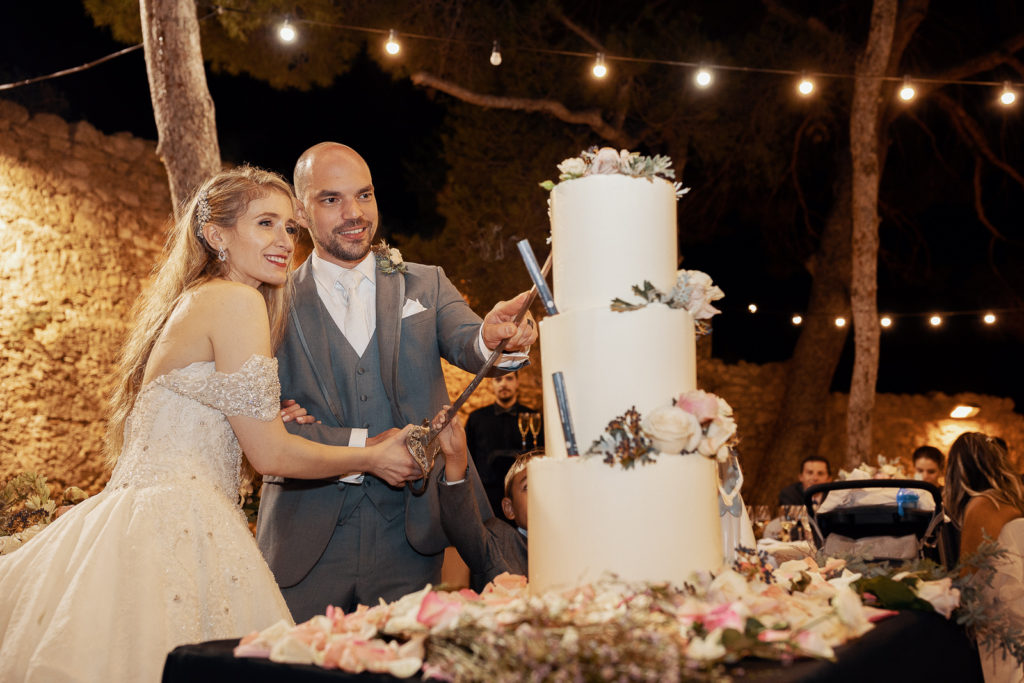bride and groom cut cake, castell de tamarit, barcelona brides