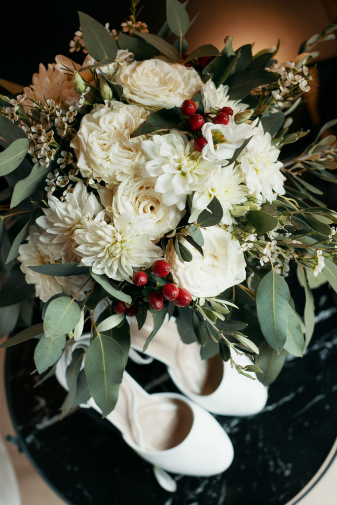 bouquet of white flowers with green leaves and red berries