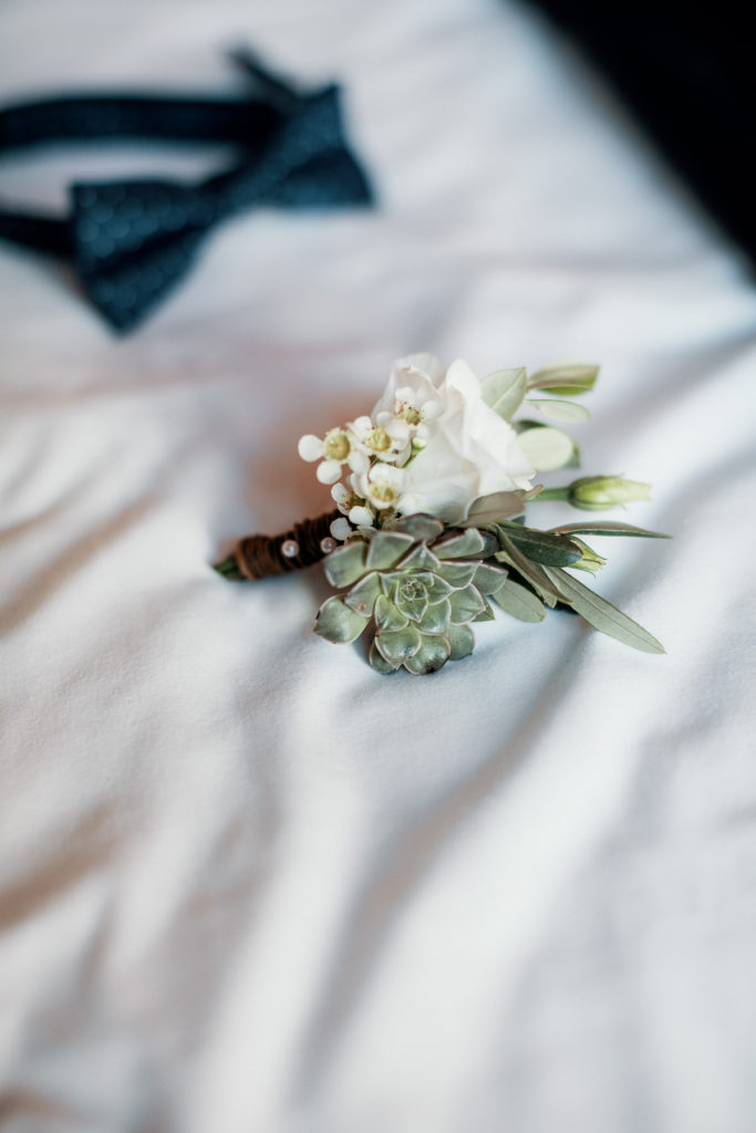 boutonniere made of white flowers and a green succulent
